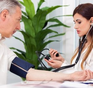 Doctor using a stethoscope and a sphygmomanometer to check blood pressure